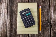 Żółty pastylka ołówek, kalkulator na rocznika biurku & obraz stock