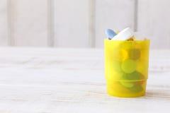Żółty pigułki pudełko wypełniał z różnorodnymi tablettes na drewnianym tle Obrazy Stock