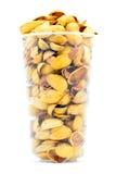Żółty pistacjowy nutshell rozsypisko w plastikowej filiżance odizolowywającej na bielu Fotografia Royalty Free