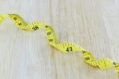 Żółty pomiarowy taśmy pojęcie dla zdrowej diety i ciężaru contro Obraz Stock