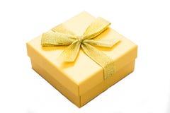 Żółty prezenta pudełko z faborkiem odizolowywającym Obrazy Stock