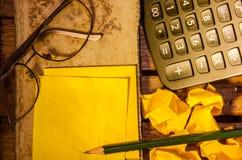 Żółty pusty papier z kalkulatorem z zmiętym papierem z szkłami z ołówkiem Fotografia Royalty Free