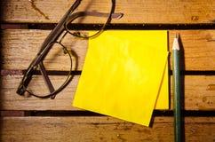 Żółty pusty papier z szkłami i ołówkiem na drewniany pettern Zdjęcia Royalty Free