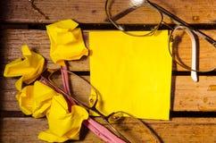 Żółty pusty papier z zmiętym papierem z dwa szkłami na drewniany pettern Fotografia Royalty Free