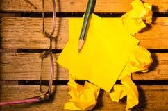 Żółty pusty papier z zmiętym papierem z szkłami i ołówkiem na drewniany pettern Zdjęcia Royalty Free
