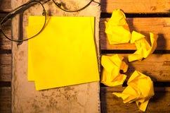 Żółty pusty papier z zmiętym papierem z szkłami na starej książce na drewniany pettern Obraz Stock