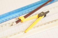 Żółty Rysunkowy kompas z pensil i władcy na wykresu papierze en Zdjęcie Royalty Free