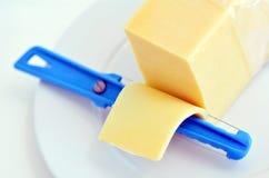 Żółty serowy plasterek i sera slicer zdjęcia stock