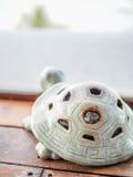 Żółwia kształt projektował popiół tacę z zamazanym białym tłem Obraz Stock