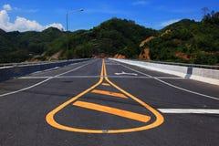 Żółta linia na autostradzie z widokiem górskim i niebieskim niebem Zdjęcia Royalty Free