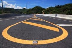 Żółta linia na autostradzie z widokiem górskim i niebieskim niebem Obraz Stock