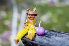Żółty Easter ceramiczny królik z purpurowym jajkiem Zdjęcie Royalty Free