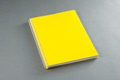 Żółty notatnik na szarym tle. Fotografia Stock