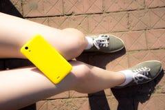 Żółty smartphone na dziewczyn nogach Obrazy Royalty Free