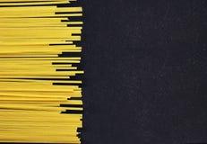 Żółty surowy spaghetti na czarnym tle Obrazy Royalty Free