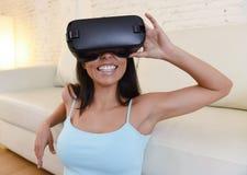 Óculos de proteção 3d de utilização entusiasmado do sofá feliz do sofá da sala de visitas da mulher em casa que olham a realidade Fotografia de Stock Royalty Free