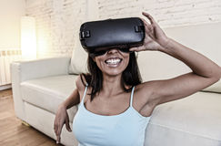Óculos de proteção 3d de utilização entusiasmado do sofá feliz do sofá da sala de visitas da mulher em casa que olham a realidade Fotos de Stock Royalty Free