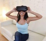 Óculos de proteção 3d de utilização entusiasmado do sofá feliz do sofá da sala de visitas da mulher em casa que olham a realidade Imagem de Stock Royalty Free