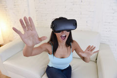 Óculos de proteção 3d de utilização entusiasmado do sofá feliz do sofá da sala de visitas da mulher em casa que olham a realidade Fotos de Stock