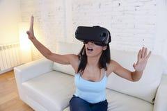 Óculos de proteção 3d de utilização entusiasmado do sofá feliz do sofá da sala de visitas da mulher em casa que olham a realidade Imagem de Stock