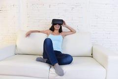 Óculos de proteção 3d de utilização entusiasmado do sofá feliz do sofá da sala de visitas da mulher em casa que olham a realidade Fotografia de Stock