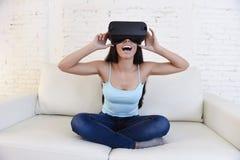 Óculos de proteção 3d de utilização entusiasmado do sofá feliz do sofá da sala de visitas da mulher em casa que olham a realidade Imagens de Stock