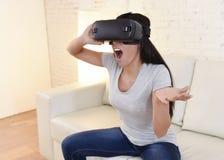 Óculos de proteção 3d de utilização entusiasmado do sofá feliz do sofá da sala de visitas da mulher em casa que olham a realidade Imagens de Stock Royalty Free