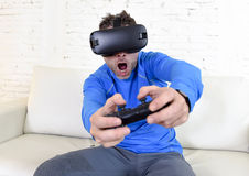 Óculos de proteção 3d de utilização entusiasmado do sofá feliz do sofá da sala de visitas do homem em casa que olham a realidade  Fotografia de Stock Royalty Free