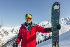 Óculos de proteção do esqui do homem novo do retrato que guardam o esqui nas montanhas Imagem de Stock