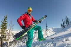 Óculos de proteção do esqui do homem novo do retrato que guardam o esqui nas montanhas Imagens de Stock