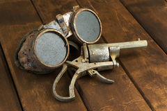 Óculos de proteção oxidados velhos do steampunk com um revólver foto de stock