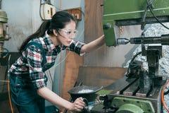 Óculos de proteção vestindo novos do trabalhador de mulher da empresa do torno imagens de stock
