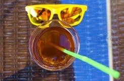Óculos de sol amarelos à moda um o vidro do chá gelado vermelho e do tubo, o conceito da bebida no café do verão A profundidade d imagem de stock