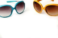 Óculos de sol azuis e amarelos em um fundo branco fotografia de stock royalty free