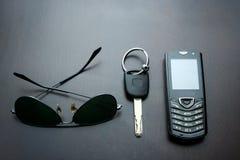 Óculos de sol, chave do carro e telefone celular em uma tabela de madeira Fotos de Stock