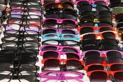 Óculos de sol coloridos na exposição na tenda Fotos de Stock Royalty Free