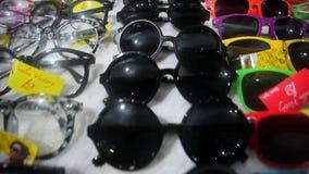 Óculos de sol coloridos na venda no mercado da cidade HD video estoque