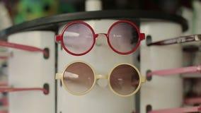 Óculos de sol coloridos para crianças na venda no mercado da cidade filme