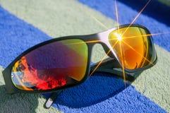Óculos de sol com brilho do sol que encontra-se em uma toalha na praia fotografia de stock