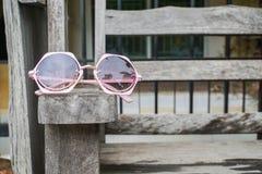 Óculos de sol cor-de-rosa bonitos das mulheres no banco de madeira imagem de stock