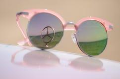 Óculos de sol cor-de-rosa contra o sol na capa de um carro com um emblema de Mercedes da estrela fotos de stock