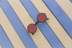 Óculos de sol criativos em uma superfície listrada Fotos de Stock