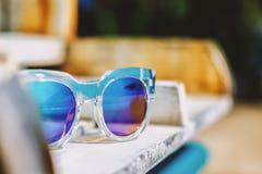 Óculos de sol da forma em uma cadeira de praia Imagens de Stock Royalty Free