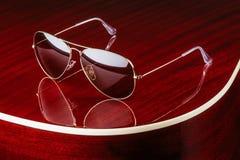 Óculos de sol do estilo do aviador na guitarra lustrosa fotografia de stock