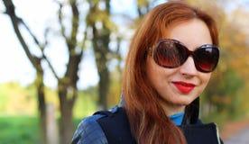 Óculos de sol do revestimento das folhas de outono da menina foto de stock royalty free