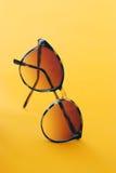 Óculos de sol do verão em um fundo alaranjado Fotos de Stock Royalty Free