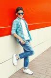 Óculos de sol e camisa vestindo de sorriso à moda do menino da criança na cidade fotografia de stock royalty free