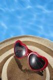 Óculos de sol e chapéu vermelhos por uma associação azul Fotografia de Stock Royalty Free