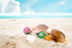 Óculos de sol e concha do mar na praia tropical arenosa com o céu azul claro fotografia de stock