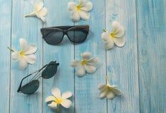 Óculos de sol e flor no fundo de madeira Foto de Stock